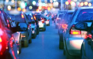 Driving a car in a city with a traffic jam at night, proceeding slow in a line of cars with red tail lights during the rush hour. view from inside the car. Blurred streets lights on the background.