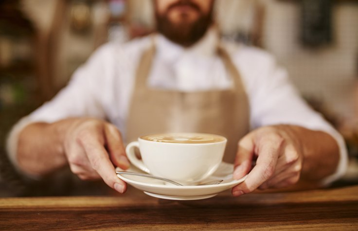 Barista serving cup of fresh coffee