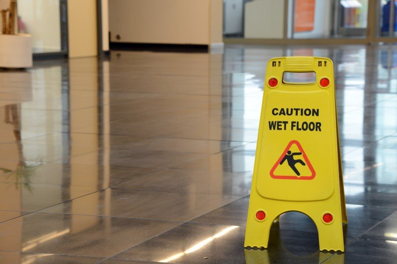 Caution wet floor sign on tiled floor | Shine Lawyers