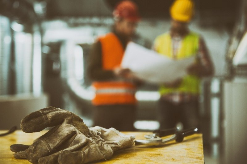 Construction glove with two workers in background | Shine Lawyers