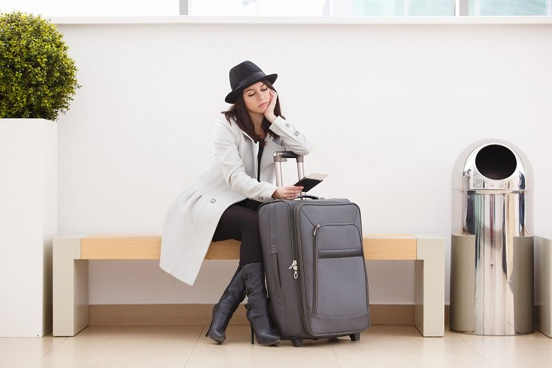 Woman waiting in a terminal | Shine Lawyers