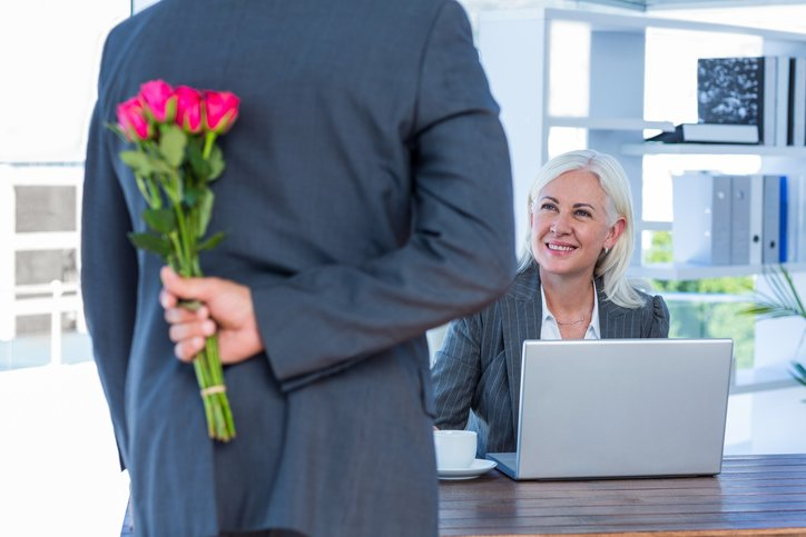 Office romance holding flowers | Shine Lawyers